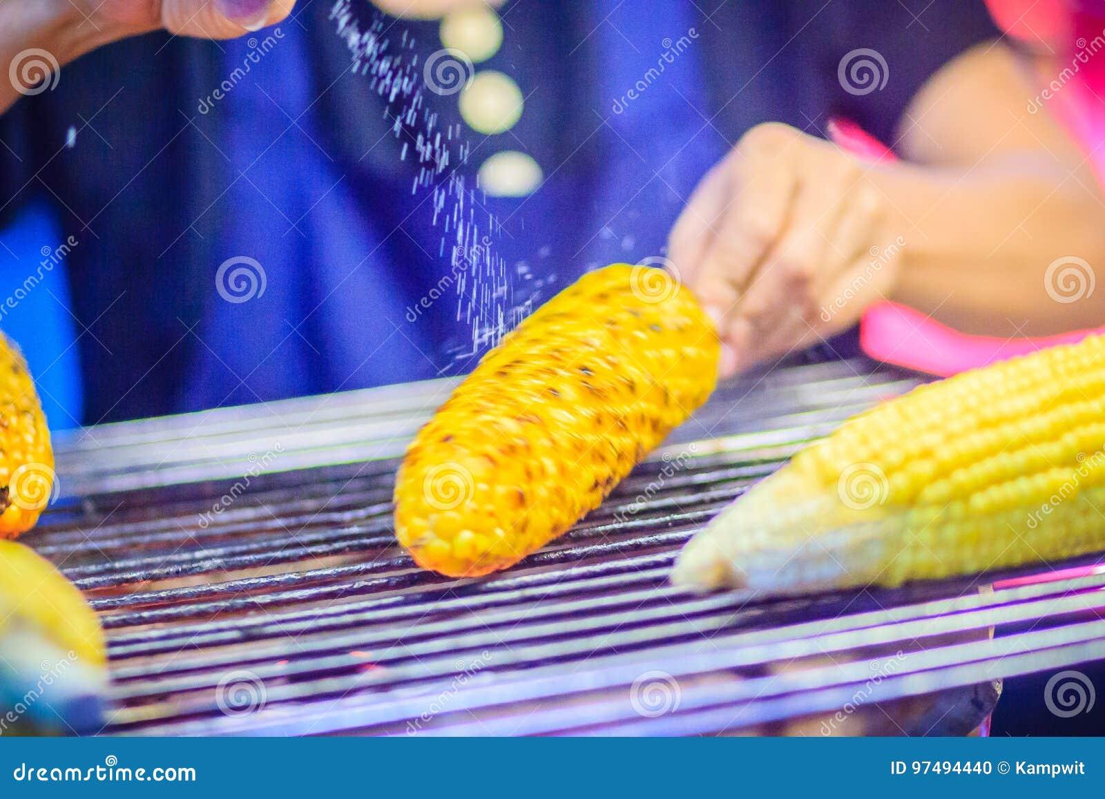 Chiuda sulla mano del venditore di alimento della via mentre grigliano per lo swe misto