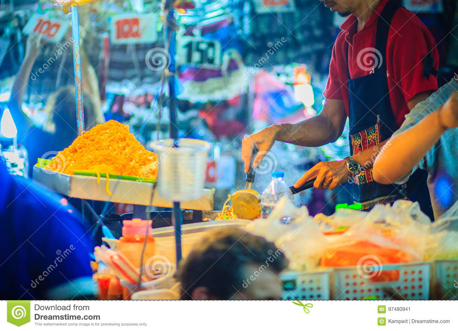 Chiuda sulla mano del venditore durante la cottura per Padthai, l originale