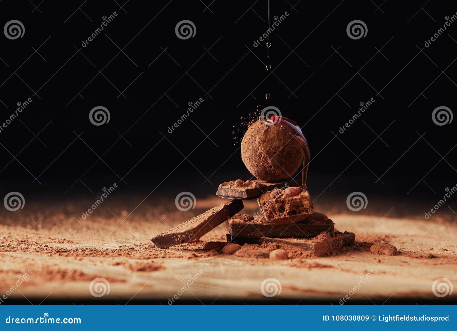 Chiuda sulla vista di caramello di versamento sul mucchio fatto delle barre di cioccolato e del tartufo