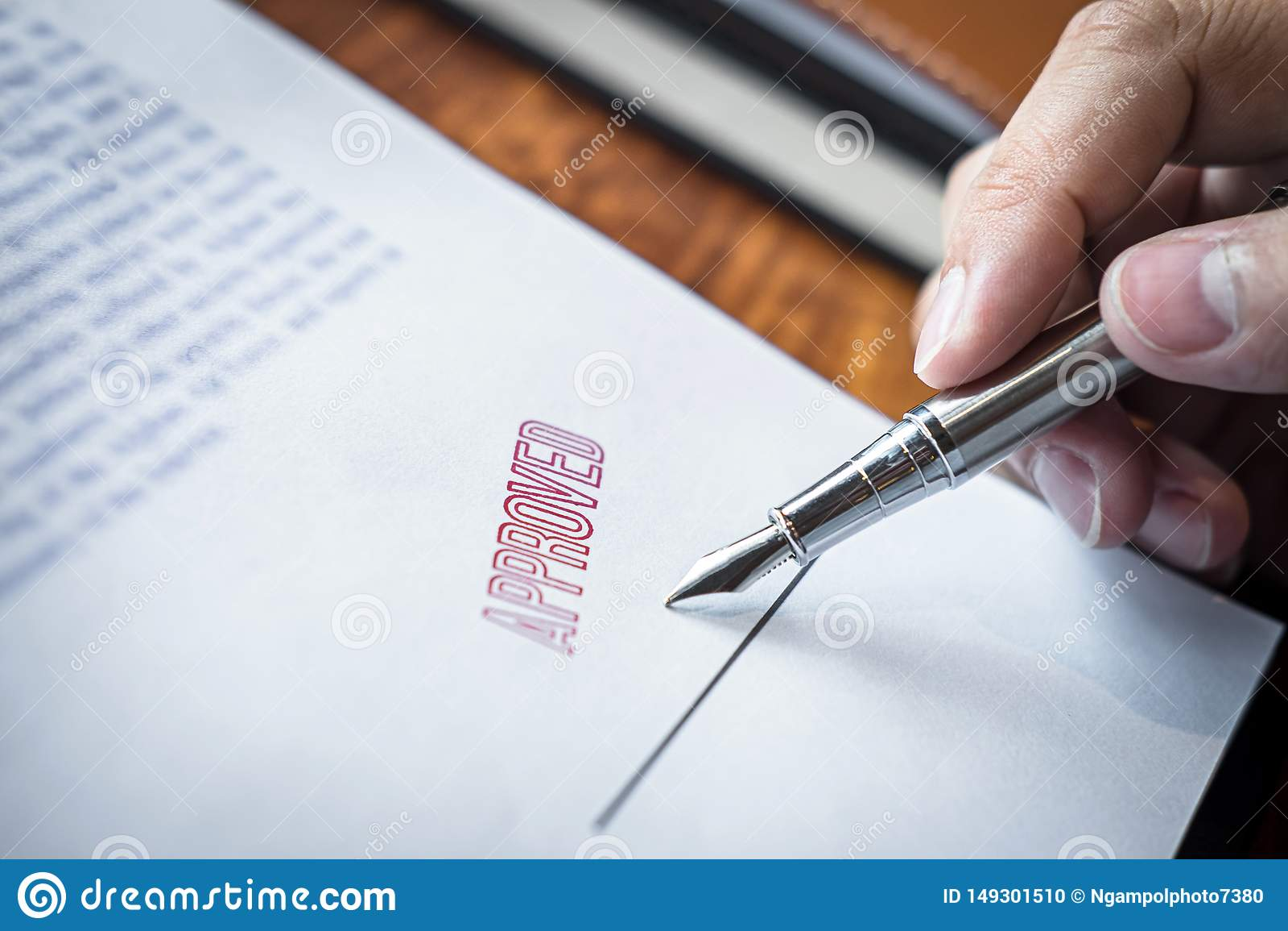 Chiuda sulle mani di firma e del bollo dell uomo d affari sul documento cartaceo per approvare l accordo di contratto di investim