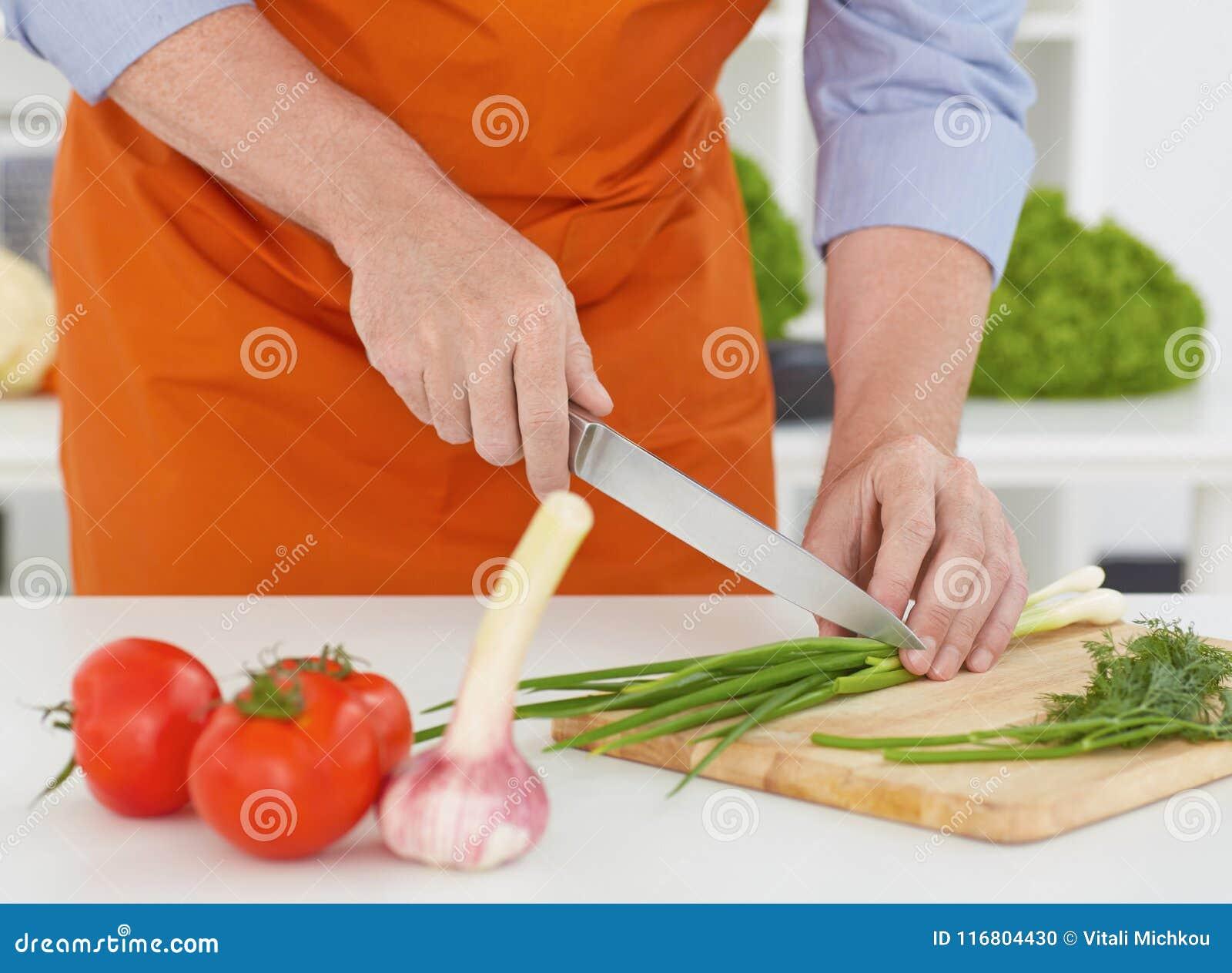 Chiuda sulle mani un uomo maturo che prepara tagliare le cipolle a pezzi verdi nella cucina a casa