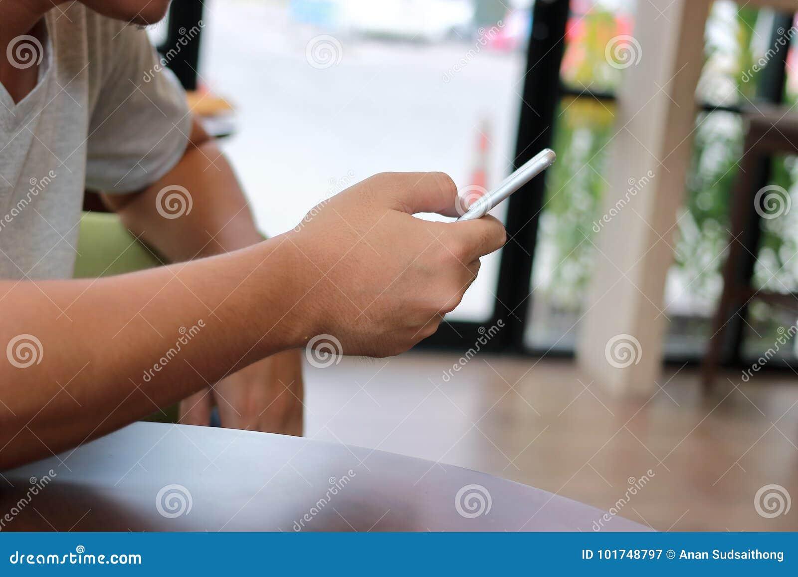 Chiuda sullo Smart Phone mobile con lo schermo in bianco sulle mani della gente non identificata in caffè del caffè