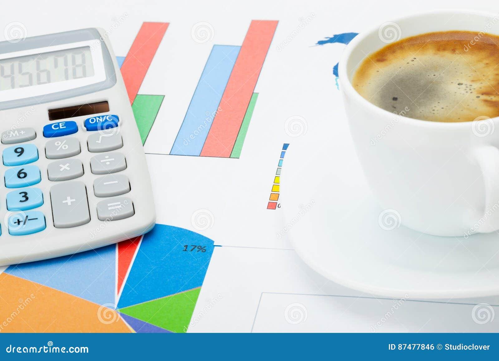 Chiuda sullo studio sparato di una tazza di caffè e di un calcolatore sopra alcuni documenti finanziari