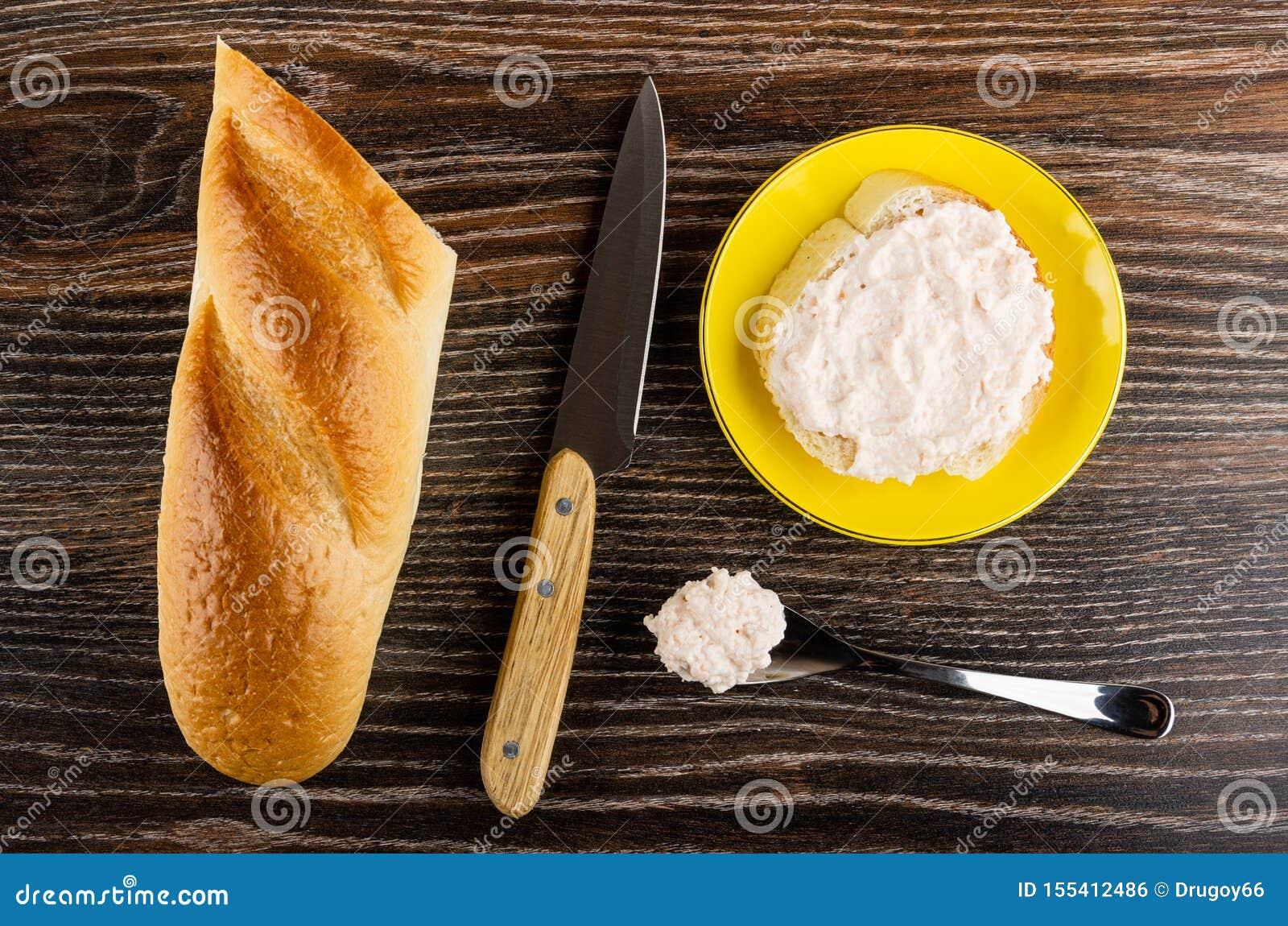 Chleb, nóż, kanapka z krill pastą w spodeczku, łyżka z pastą na drewnianym stole Odg?rny widok