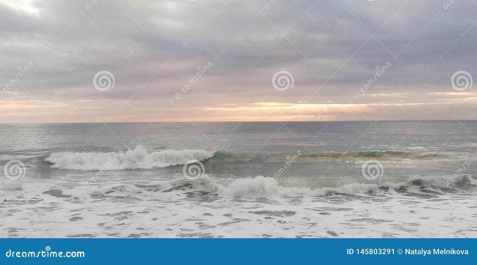 Chmurnieje ciemnego seascape nieba zmierzch S?o?ce ?ama przez niskich ci??kich chmur