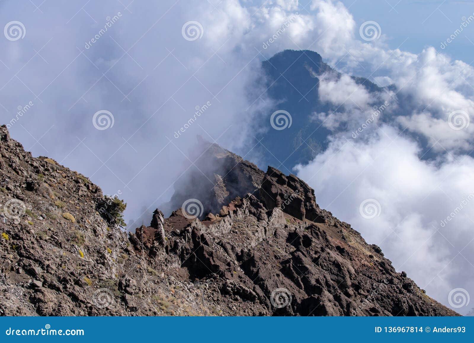 Chmury tworzy nad powulkaniczną granią i górami przy Roque De Los Muchachos na losie angeles Palma, wyspy kanaryjskie