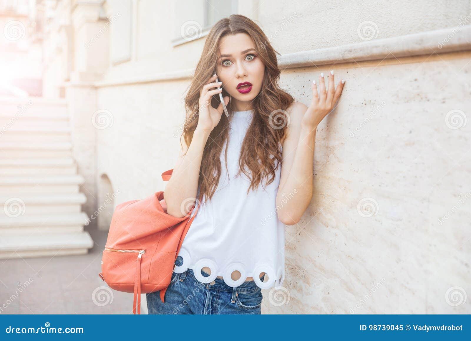 Chockad härlig ung kvinna som utomhus rymmer hennes smartphone