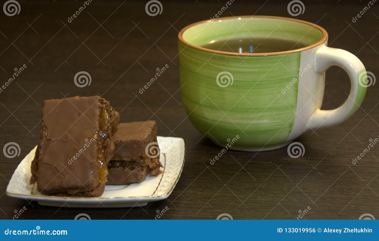 Chocoladebiscuitgebak op een witte porseleinplaat en een kop thee