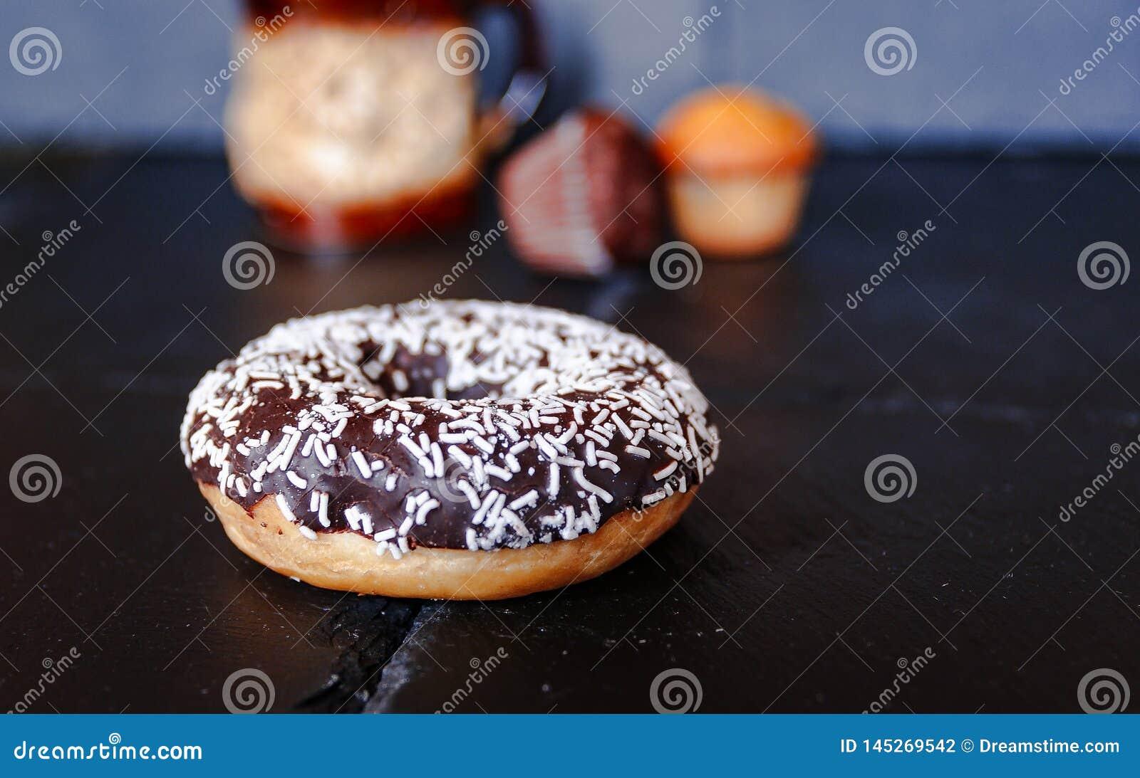 Chocoladedoughnut met muffins op achtergrond