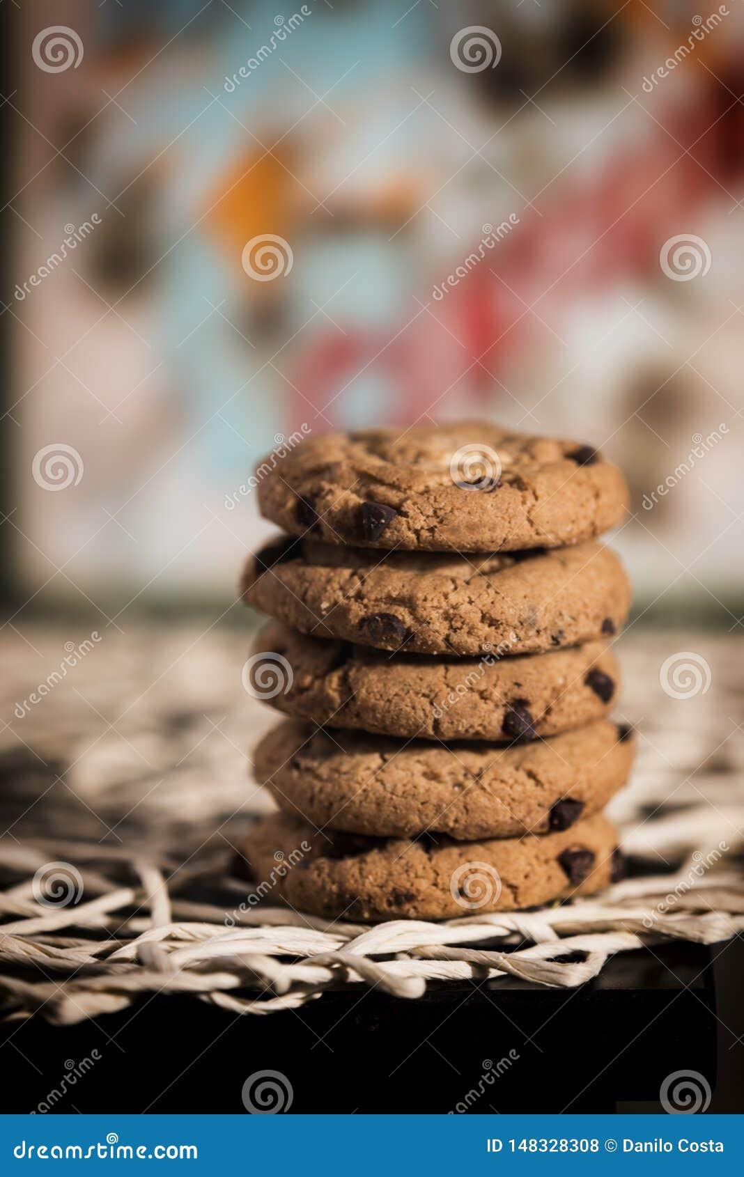 Chocoladekoekjes op belangrijkste voorwerpen, gekleurde achtergrond en bokeh