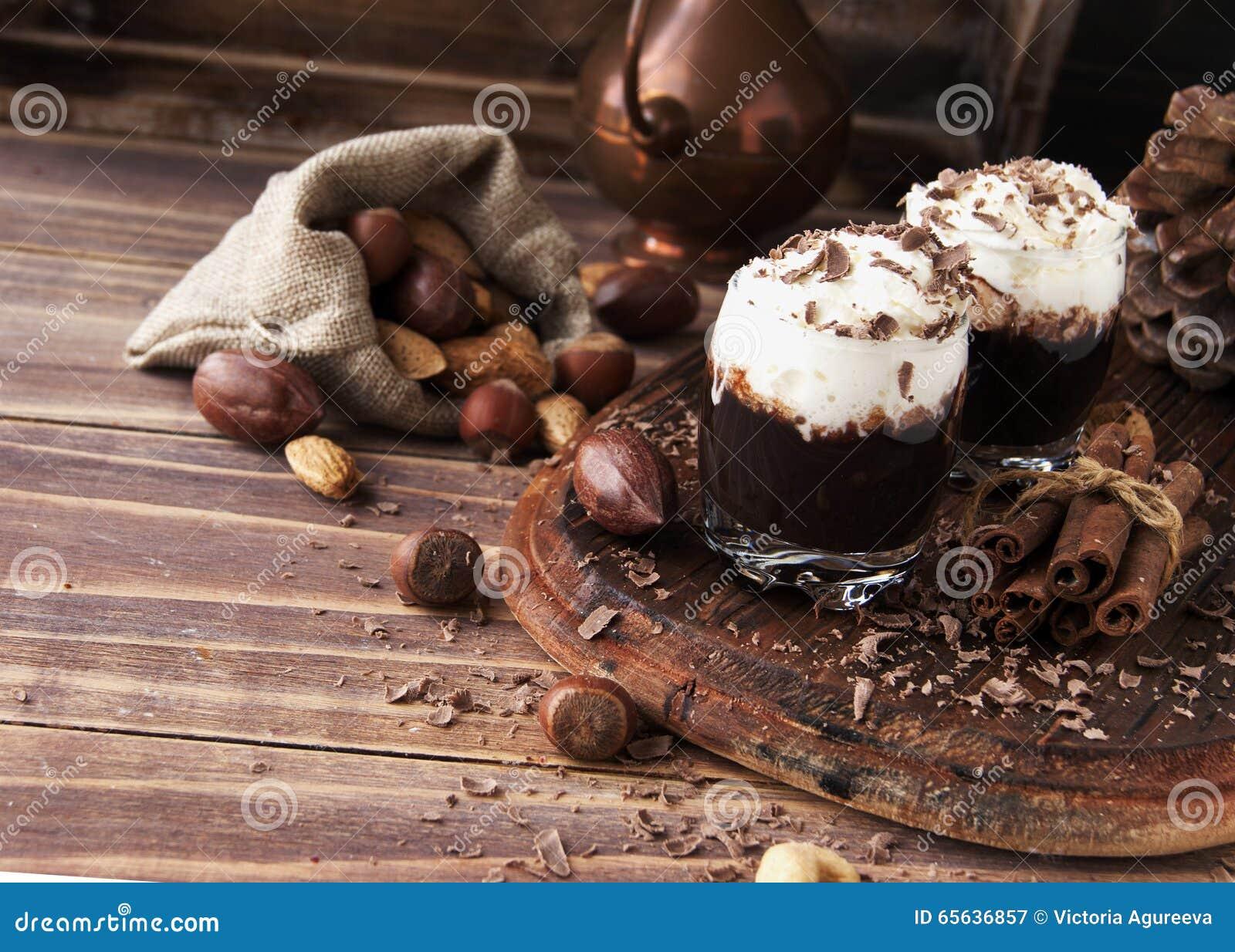Chocolat chaud en tasses et crème en verre avec des écrous