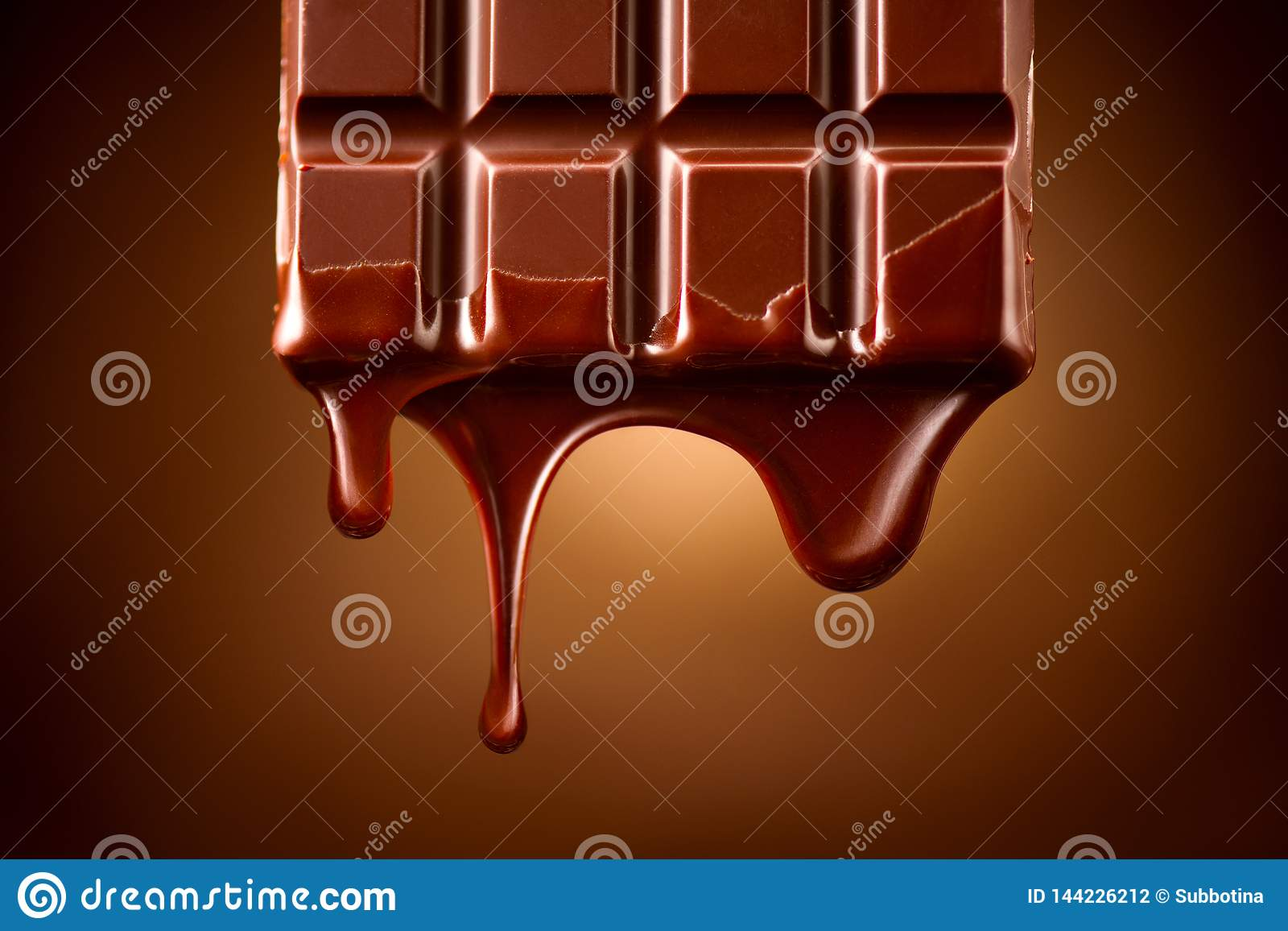 Chocolate bar with melted dark chocolate dripping over dark brown background. Confectionery concept backdrop. Melted chocolate