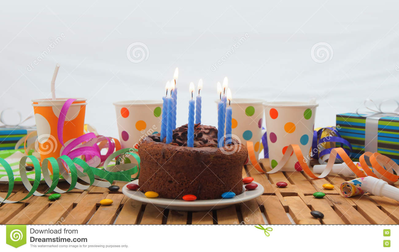 Chocolate Birthday Cake With A Blue Candles Burning On Rustic Wooden Table Background Of Colorful