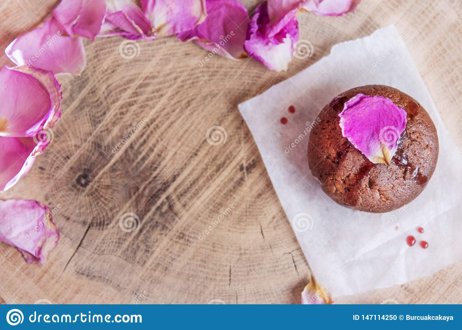 Chocolate cake on a baking paper served with rose petals on a wooden sevice plate, above vanta