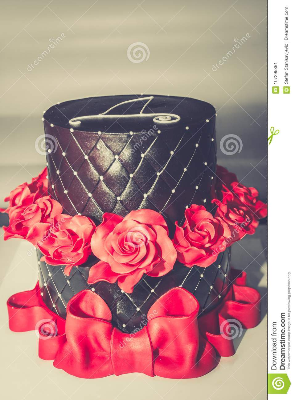 chocolate birthday cake with red roses big red ribbon and cyrillic letter d on the top copy space
