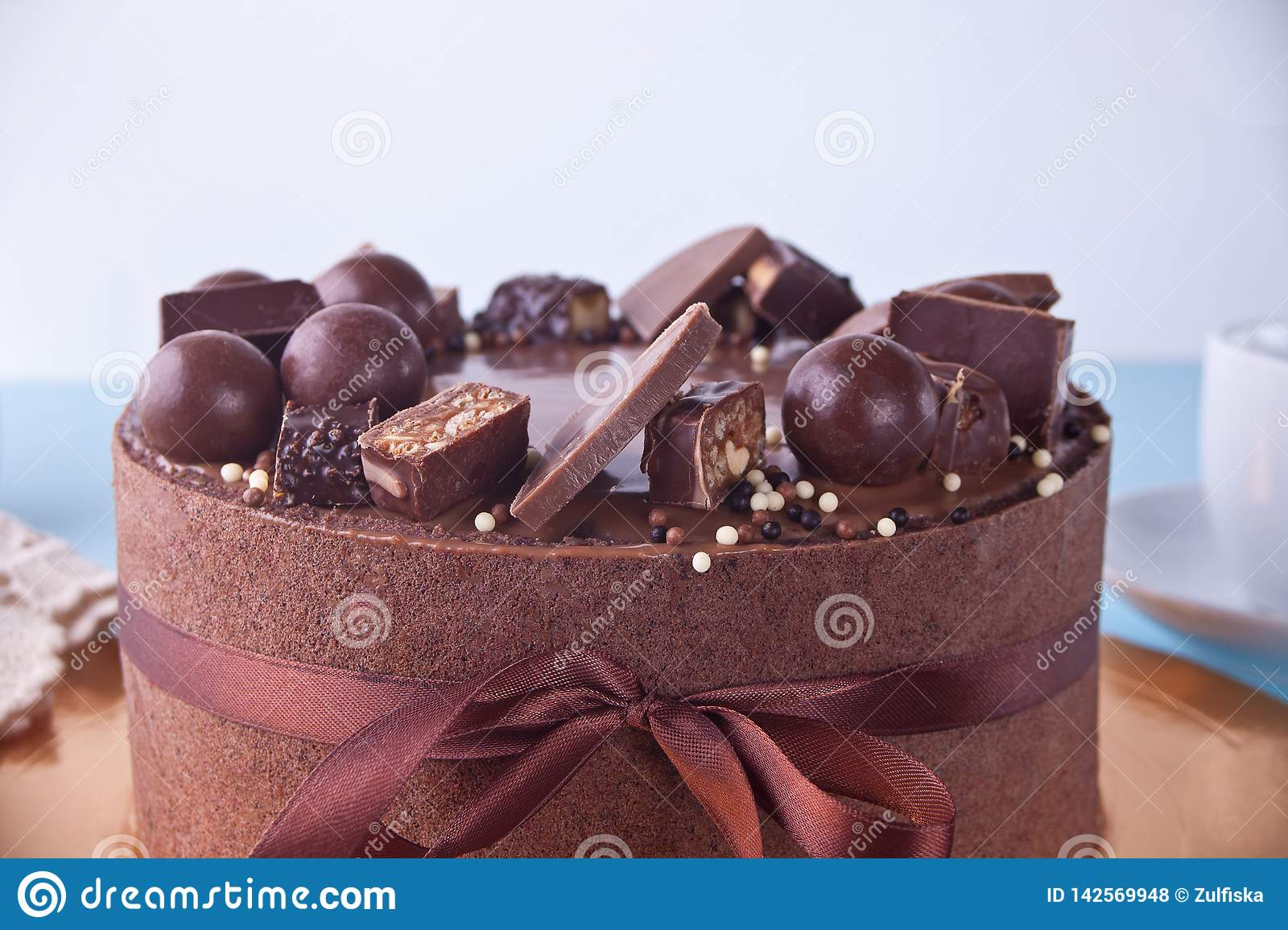 Chocolate Cake With Candy And Ribbon On A Blue Table Stock