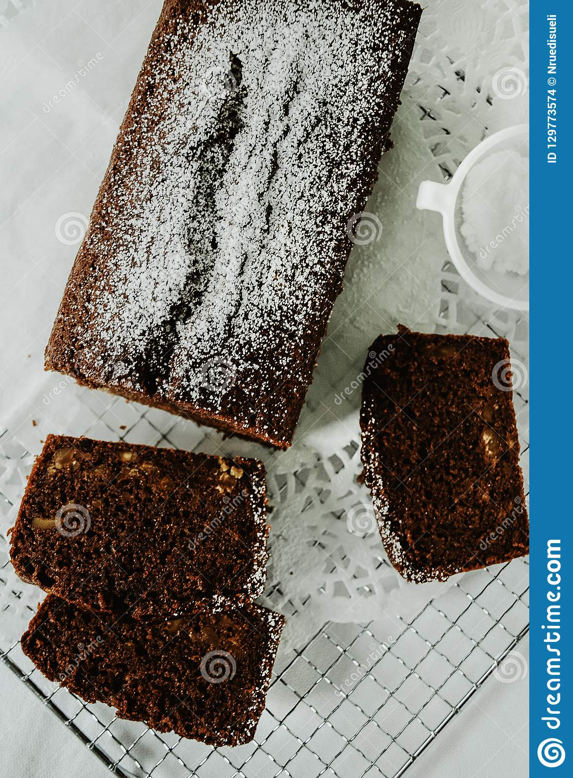 Chocolate cake with nuts inside cut into slices on cooling rack.