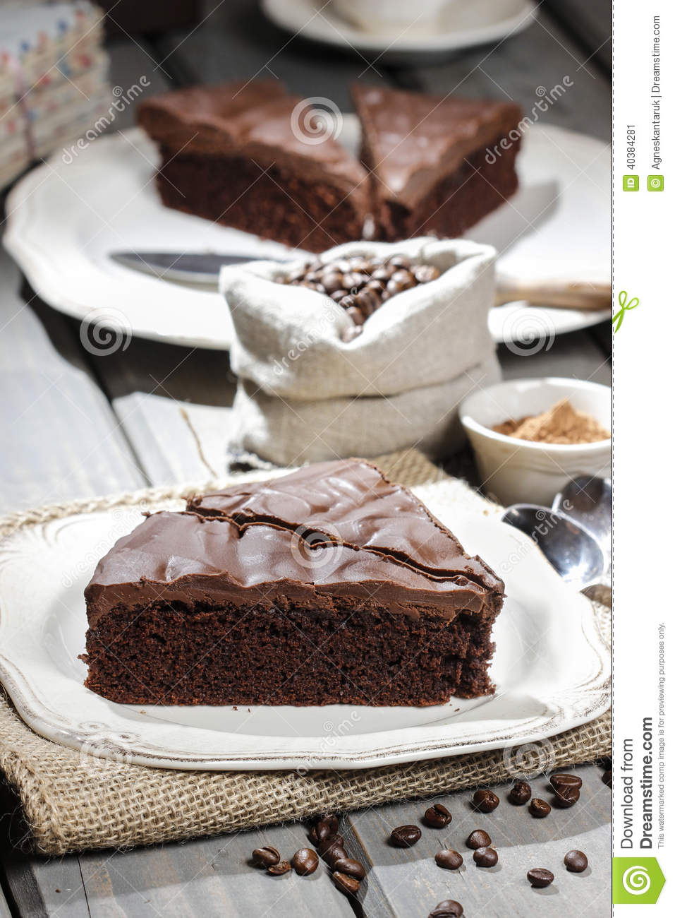 Chocolate cake on white plate, on hessian
