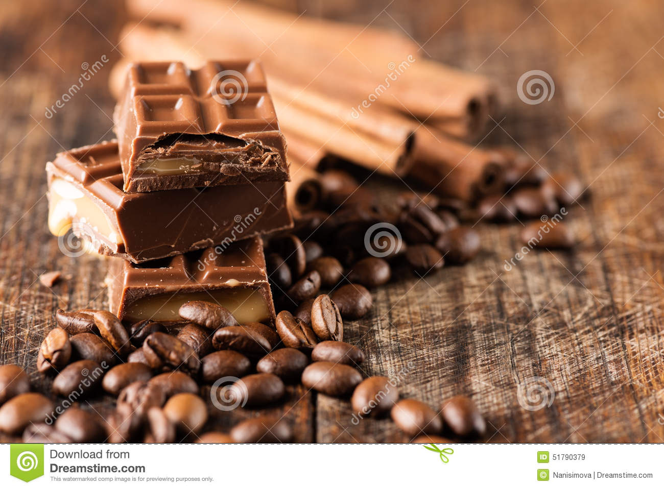 chocolate candy bar cofee beans cinnamon on wooden table