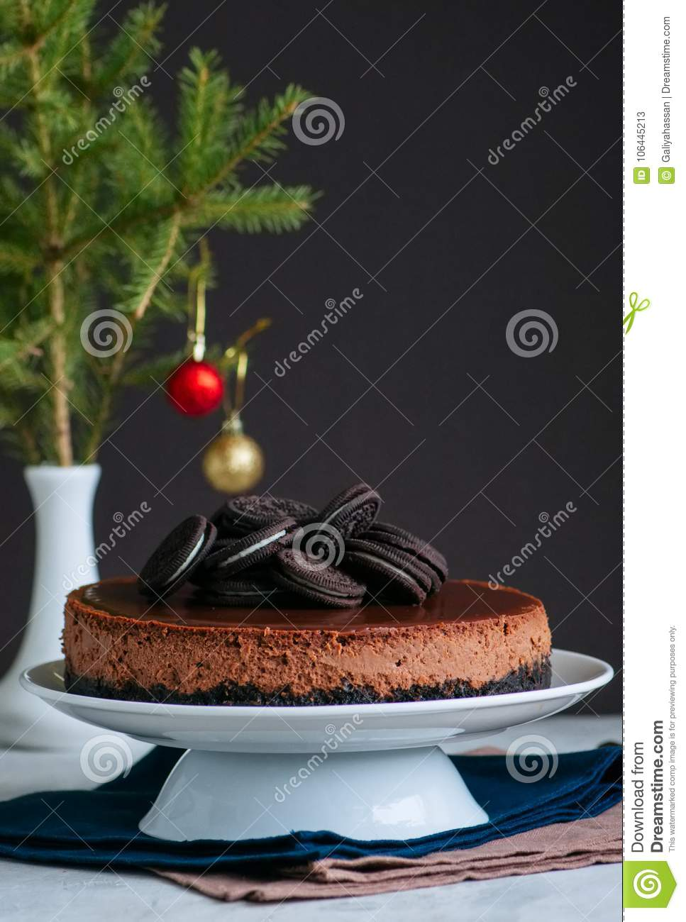 Chocolate cheesecake with cookies on a white plate. Festive baking.