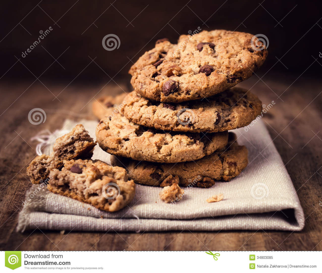Chocolate chip cookies on linen napkin on wooden table. Stacked