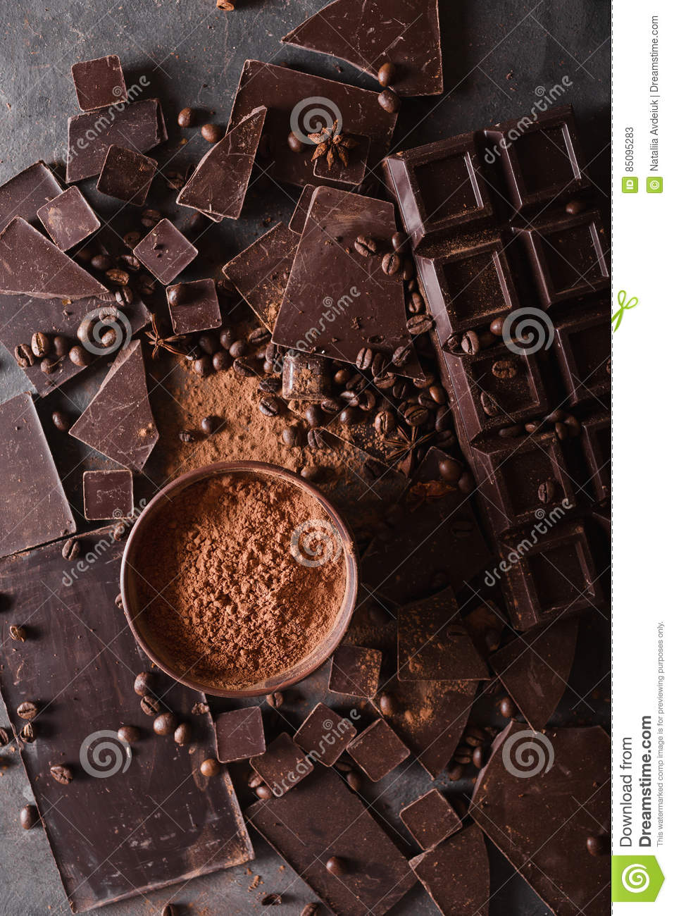 Chocolate chunks and cocoa powder. Coffee beans Chocolate bar pieces. Large bar of chocolate on gray abstract background.
