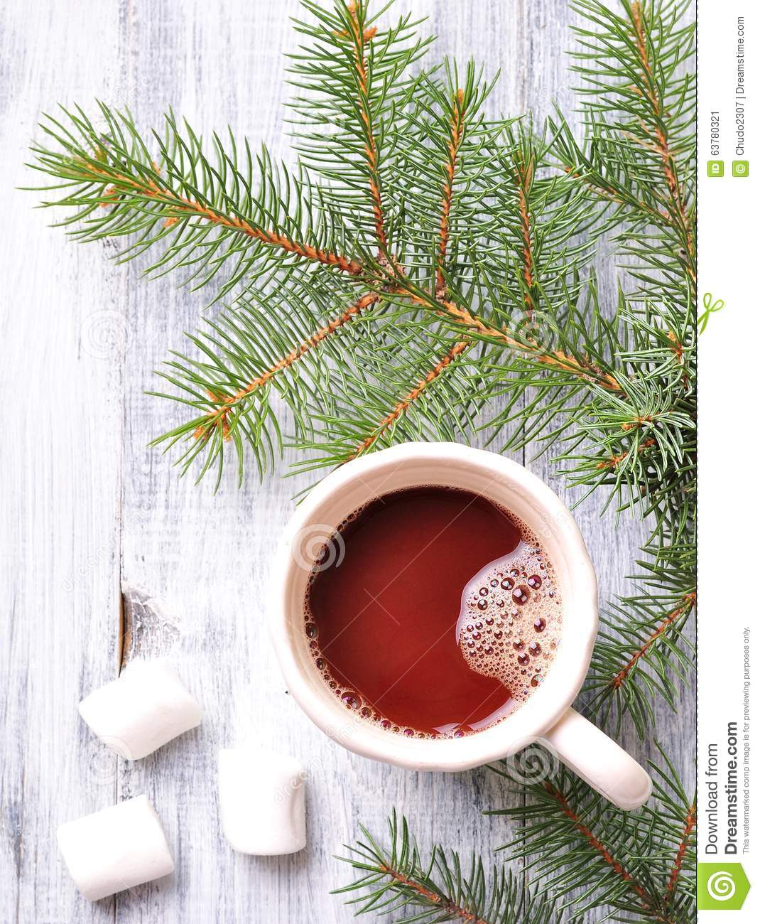 Chocolate or cocoa drink with marshmallows in a Christmas cup on the background of spruce