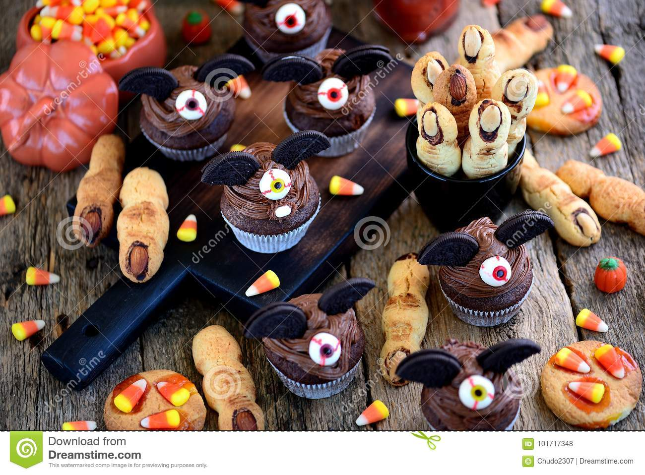 Chocolate cupcakes `bats` and shortbread cookies `witch`s fingers` - delicious bakery sweets for the celebration of Halloween.