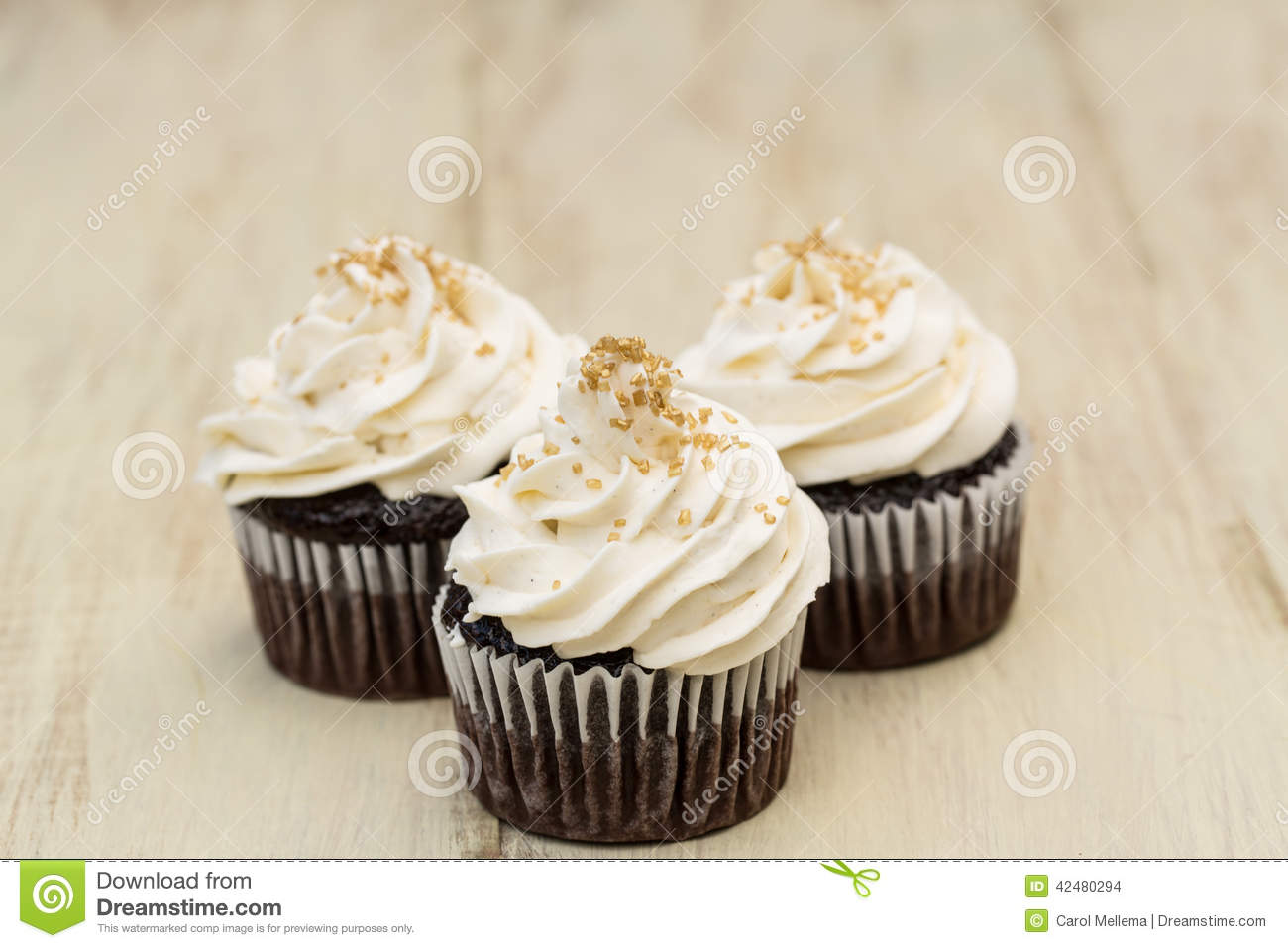 Chocolate Cupcakes With White Icing And Gold Sprinkles Stock Photo ...