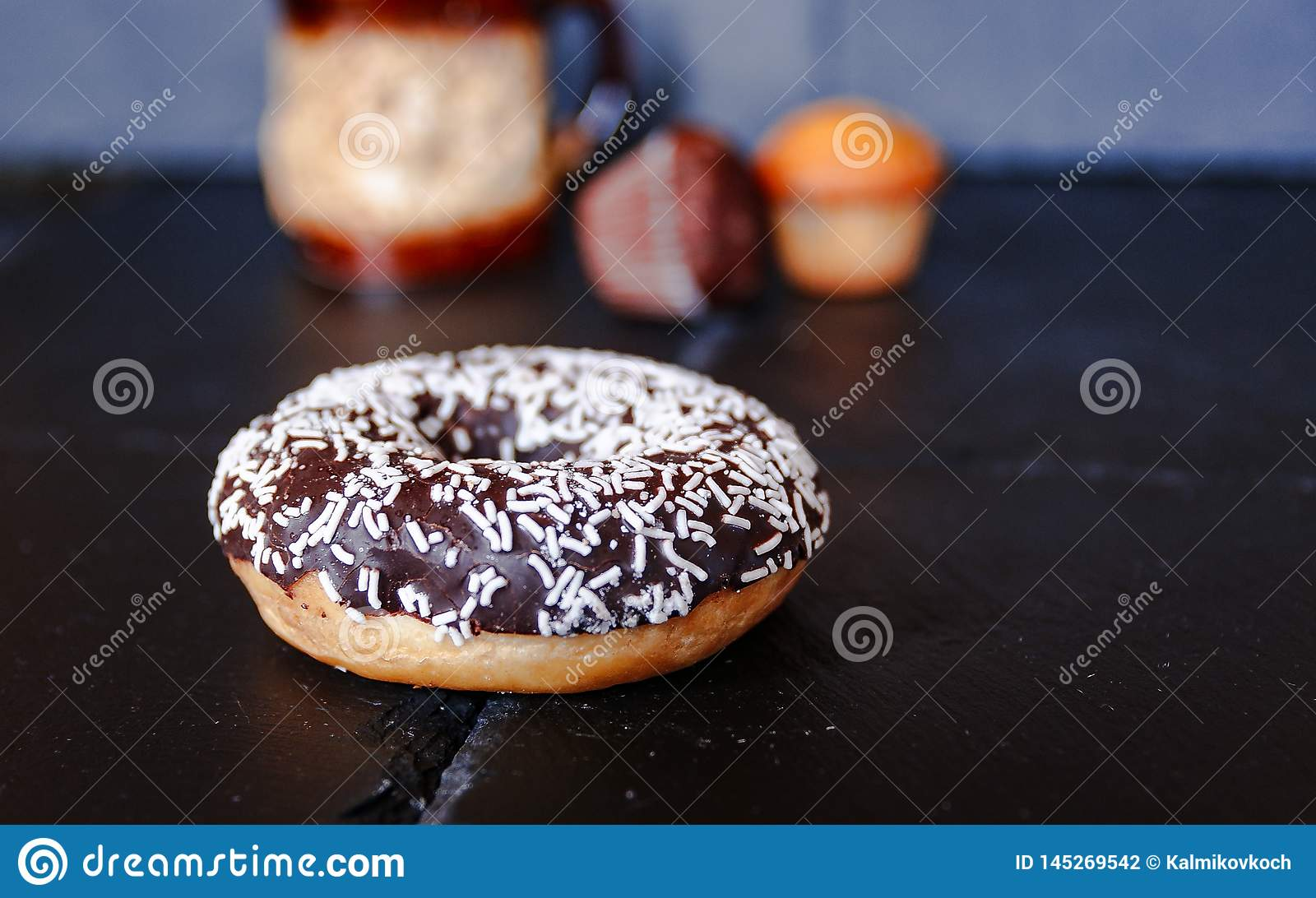 Chocolate donut with muffins on  background.