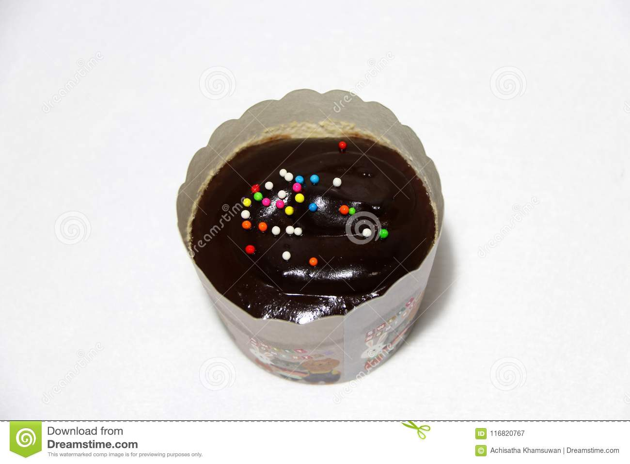 Chocolate flavor of cup cake on the white background with colorful rounded sugar beads on the top.