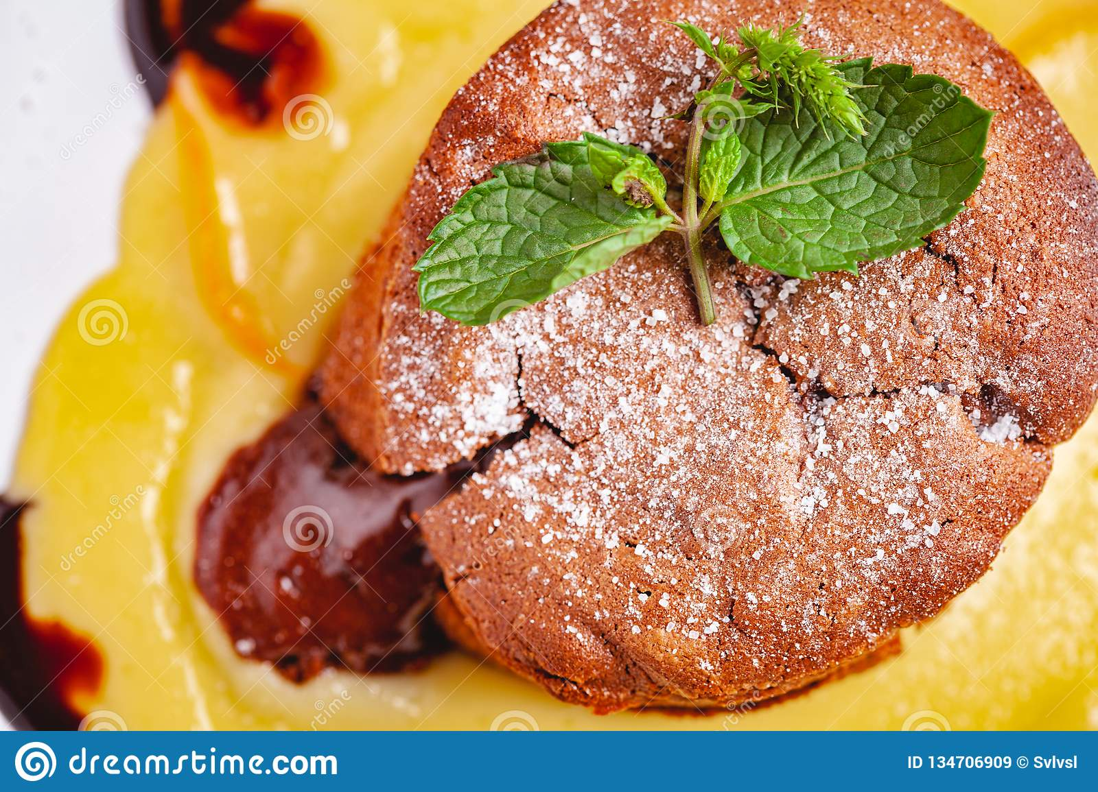 Chocolate fondant served with custard cream on white plate. Lava cake recipe. Top view
