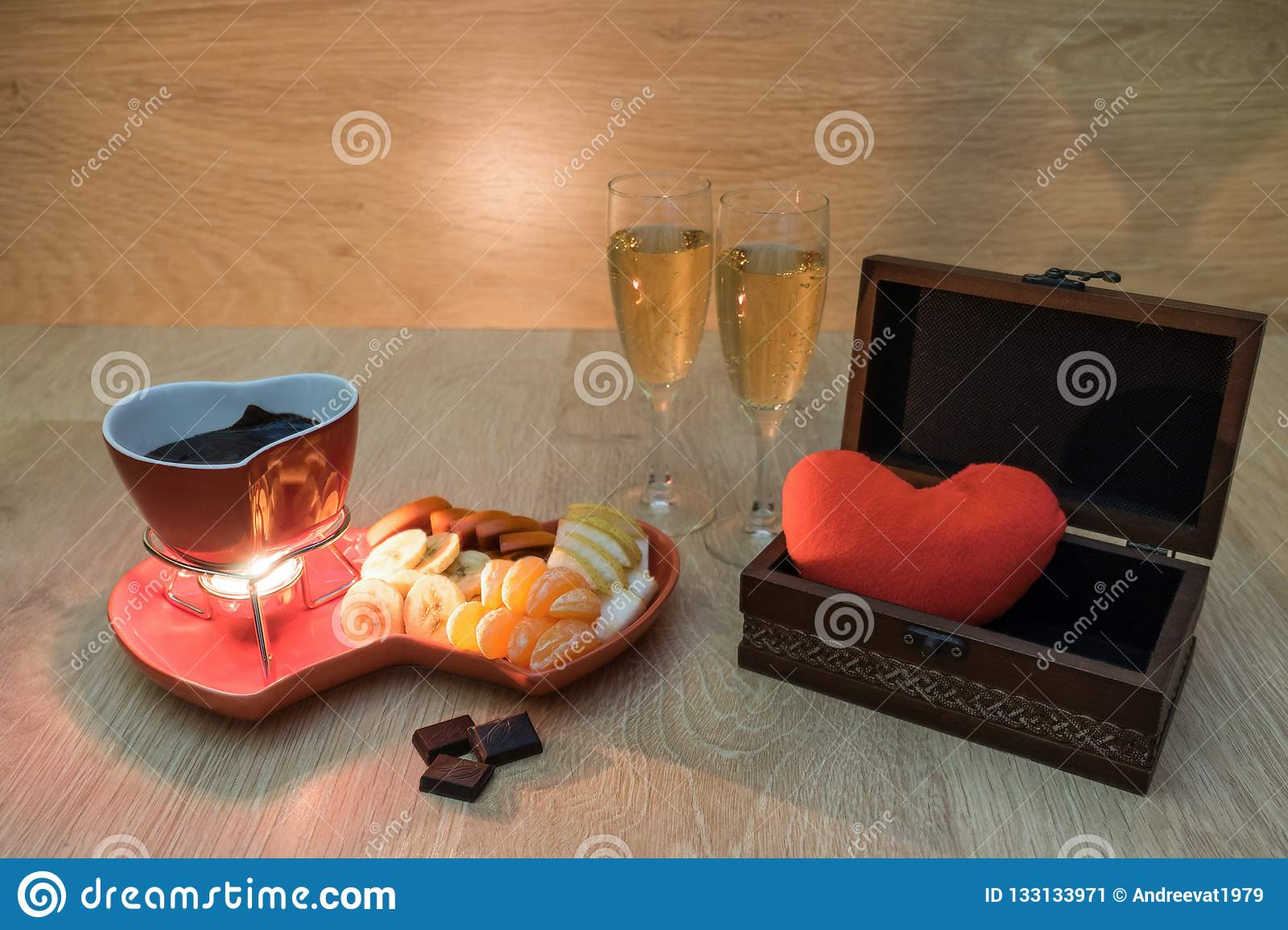 Chocolate fondue with fruit and champagne and a gift box with heart. Romantic dinner. Love, romance or Valentines day concept
