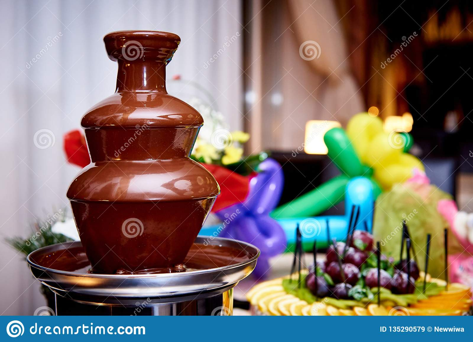 Chocolate fountain on a blurred background with fresh fruits
