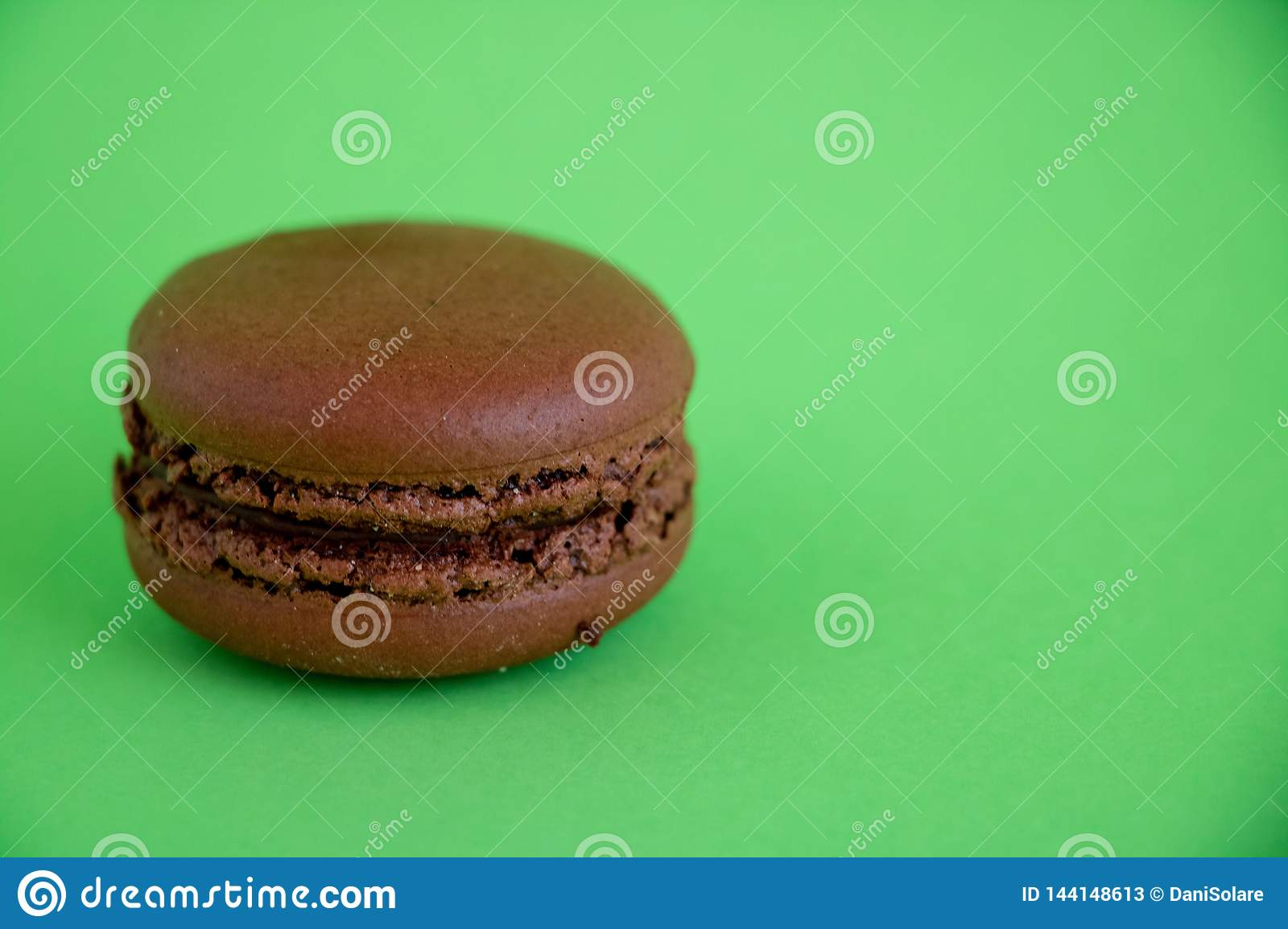 Chocolate macaroons on green background.