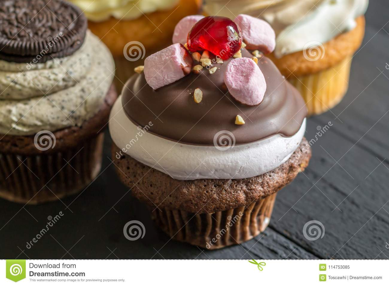 Chocolate And Marshmallow Decorated Cup Cake With Cherry On Top Cupcakes In Background Rustic Black Tablen