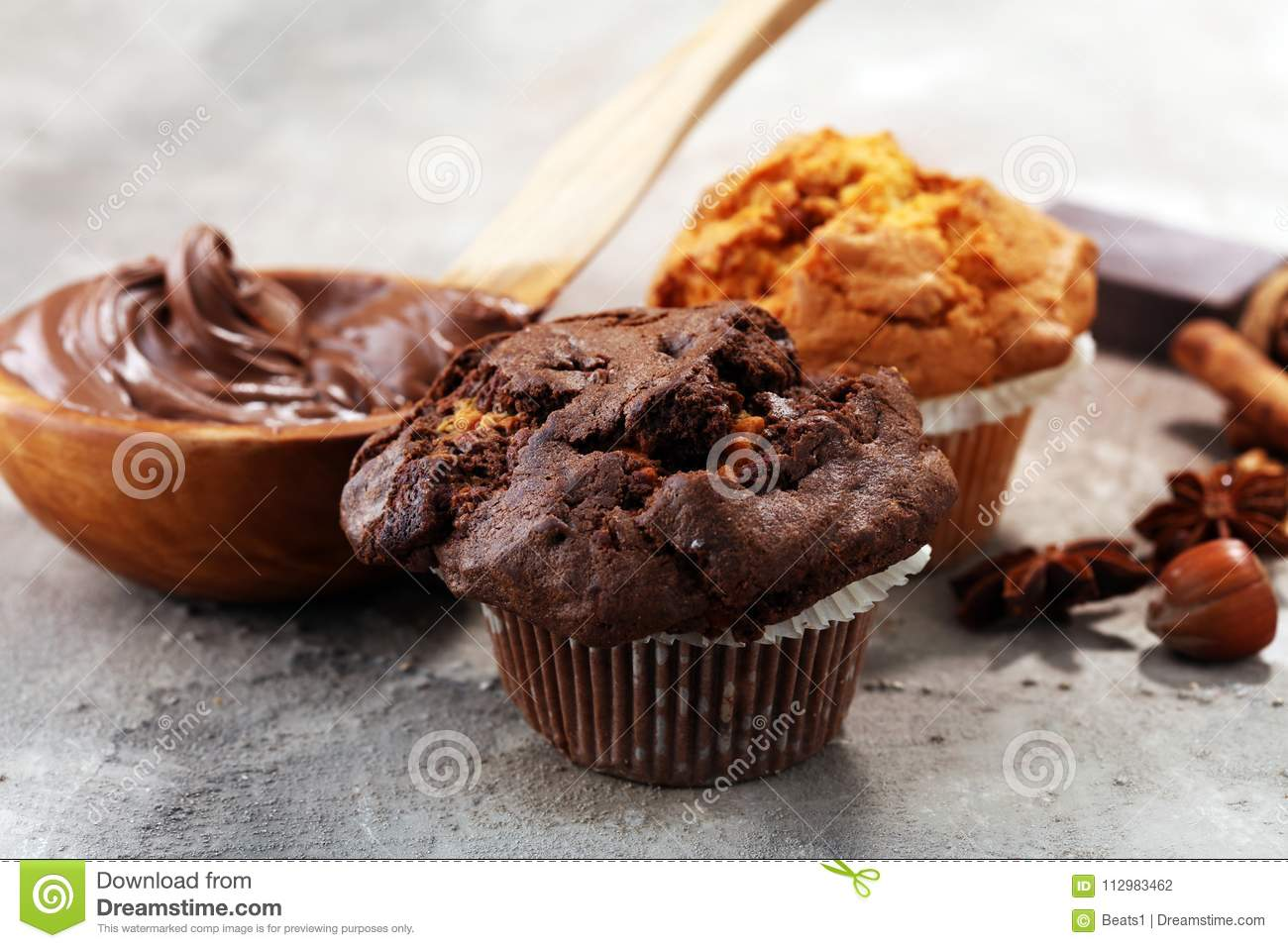 Chocolate muffin and nut muffin, homemade bakery on grey background
