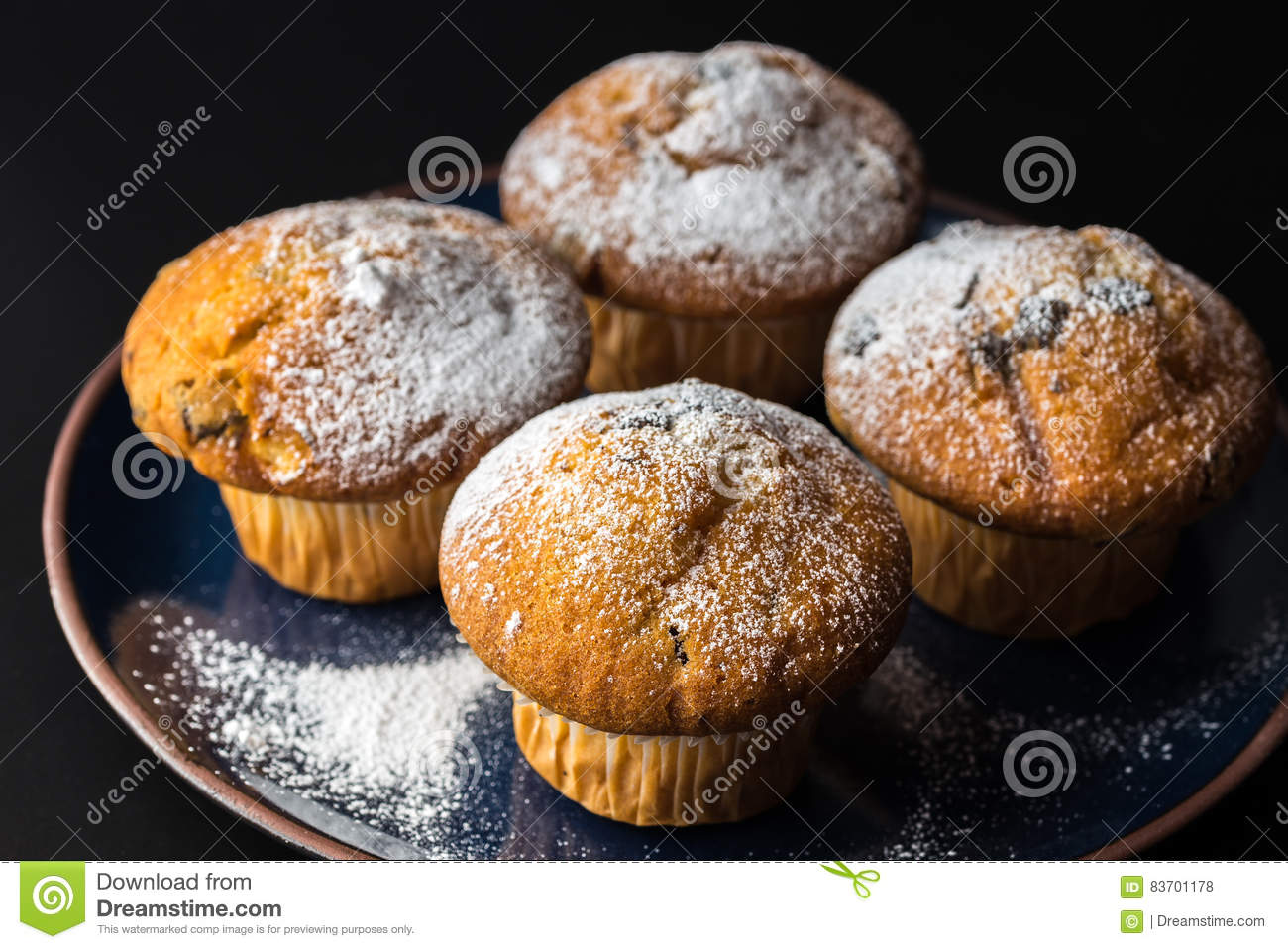 Chocolate Muffins With Powdered Sugar On Dark Blue Plate. Stock Photo