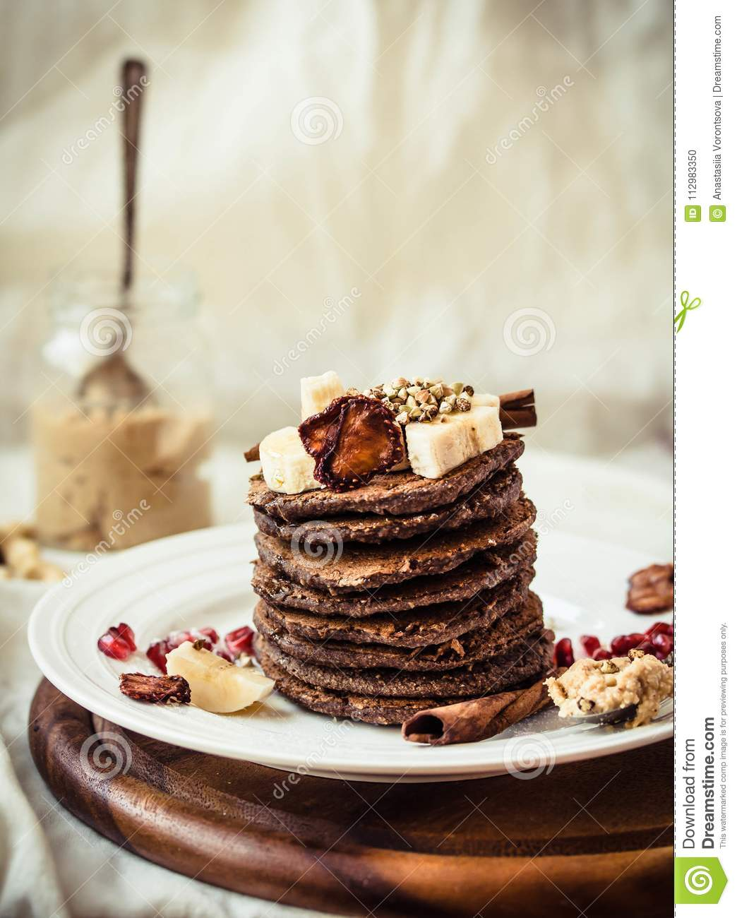 Chocolate pancakes with banana, peanut butter, cinnamon and maple syrup. A healthy breakfast for children.