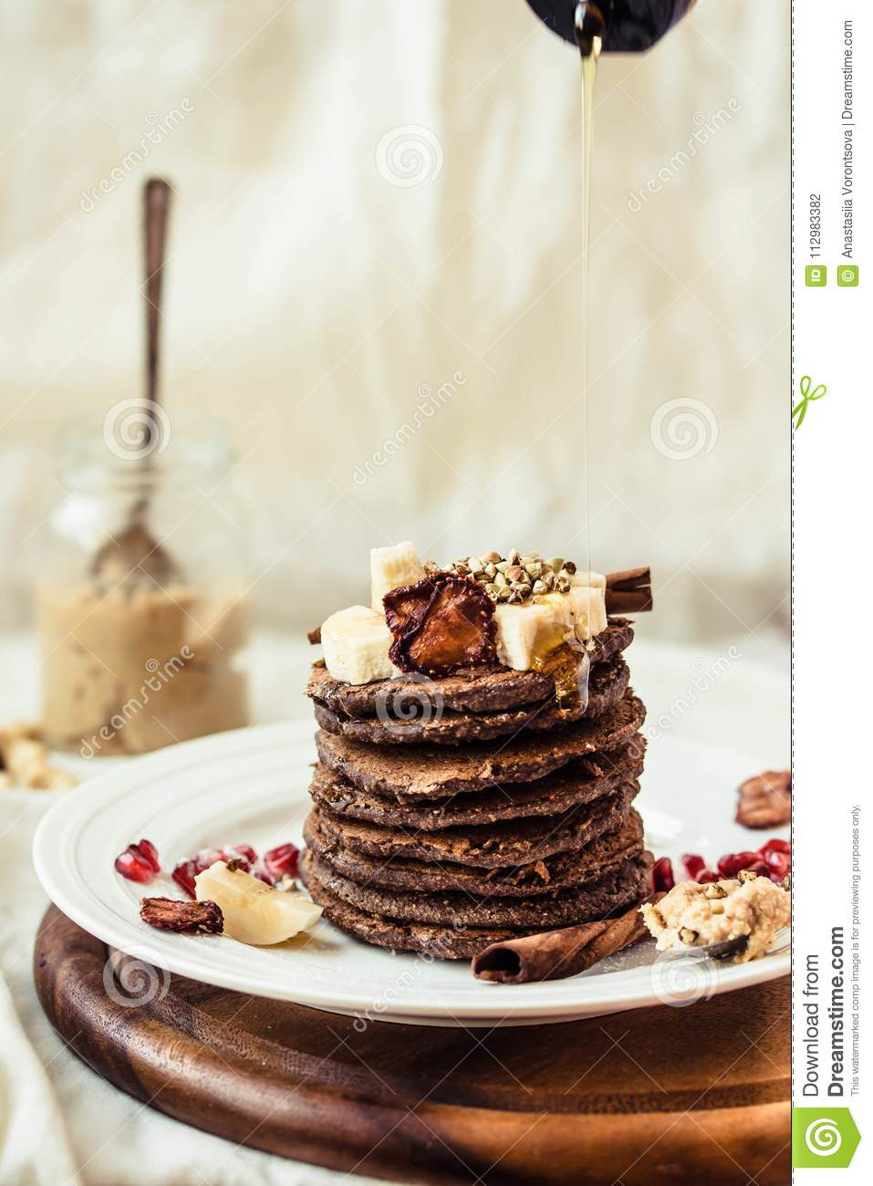 Chocolate pancakes with banana, peanut butter, cinnamon and maple syrup pour.Selective focus.Place for text