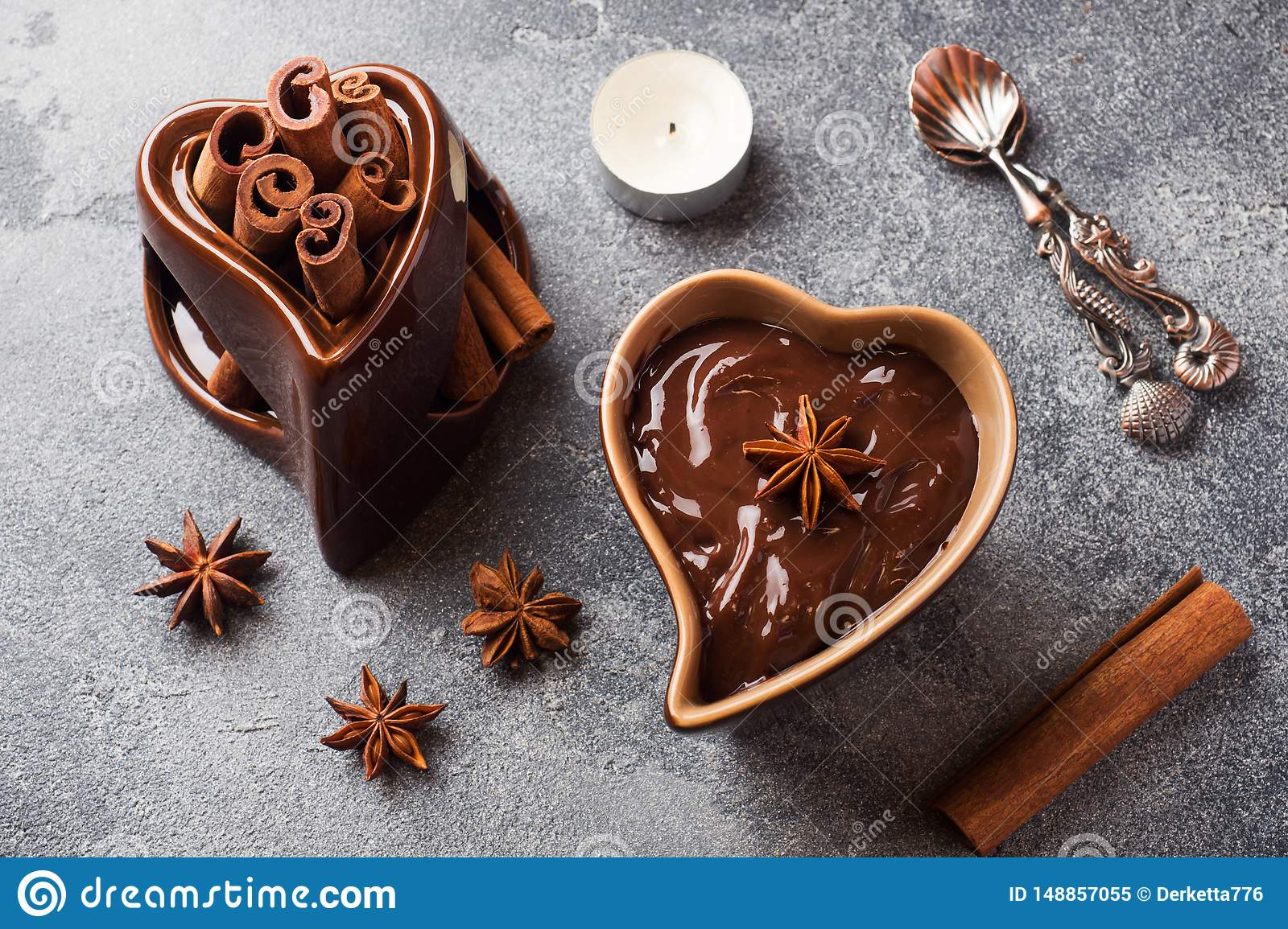 Chocolate paste with cinnamon and anise. Fondue with chocolate on a dark concrete table