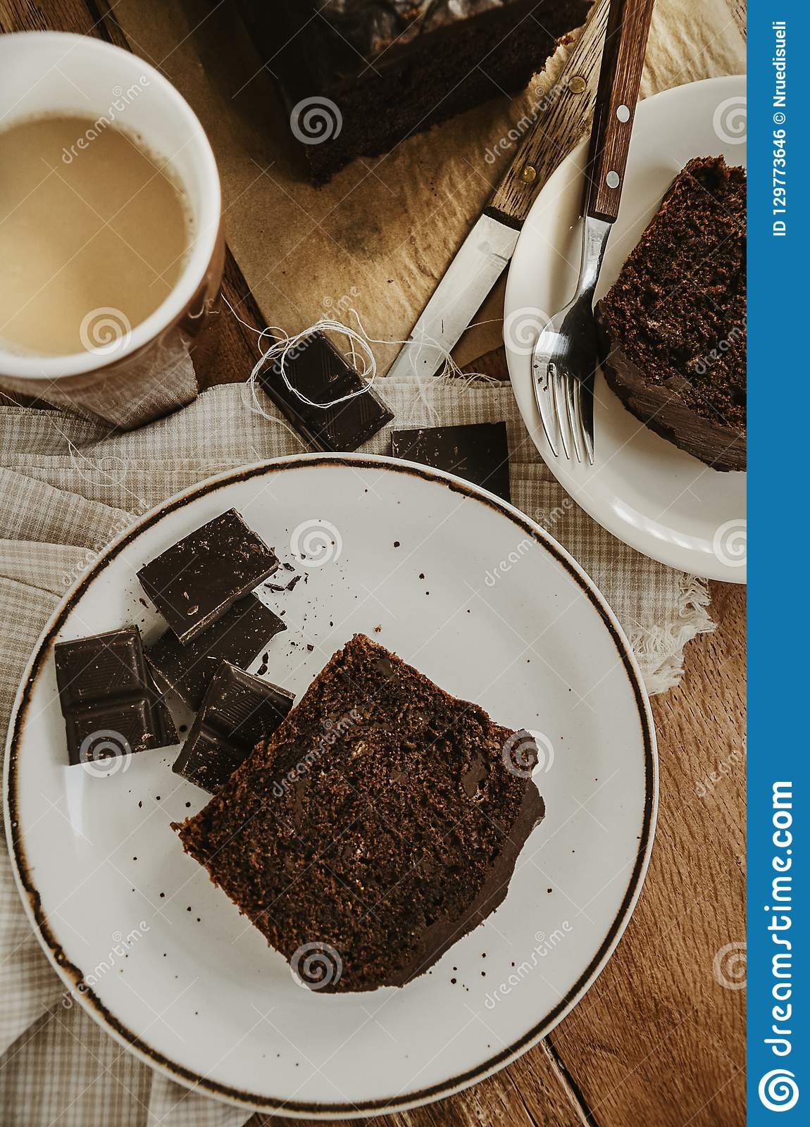 Chocolate pound cake pieces on white plates. Brown toned.
