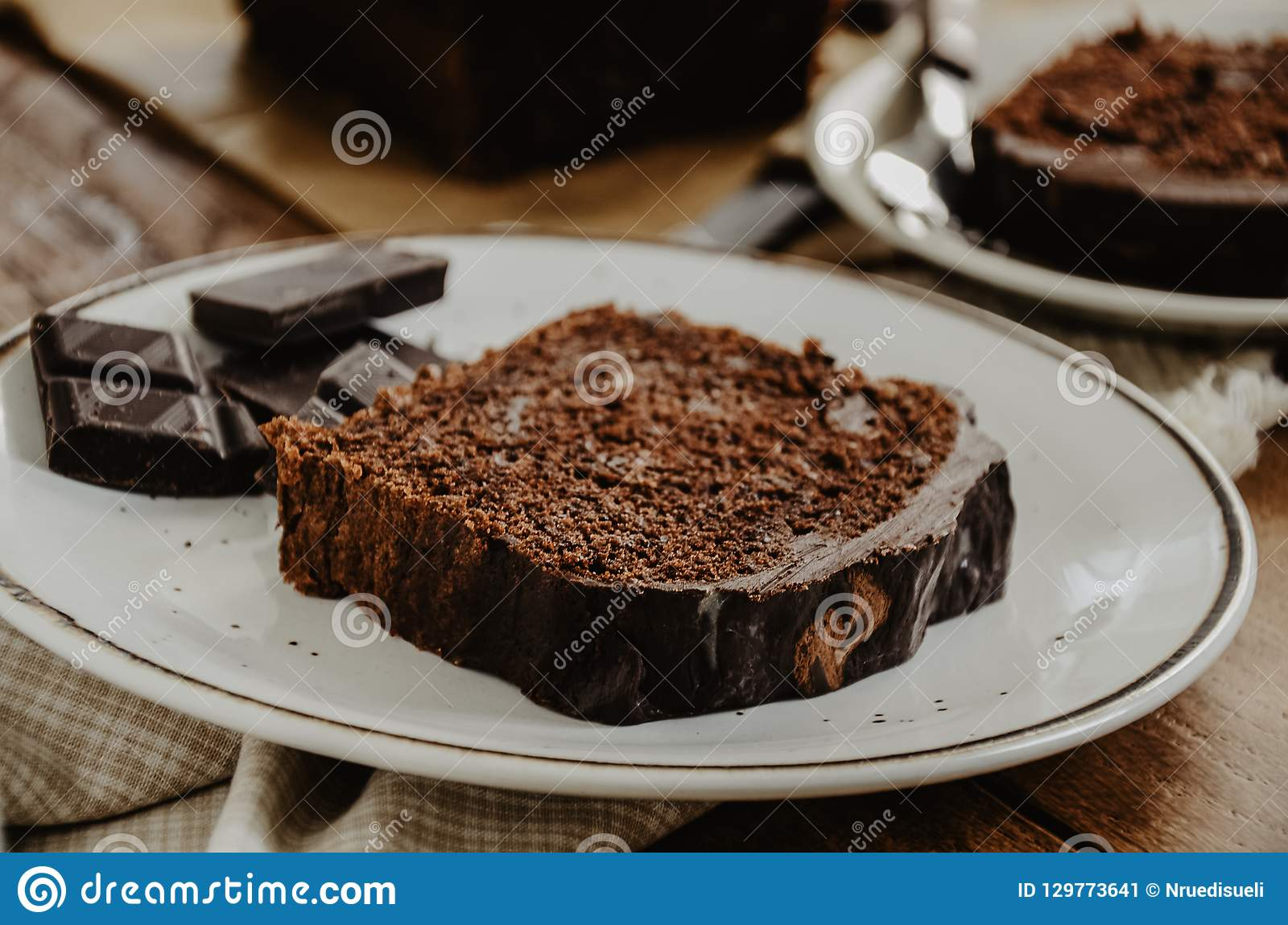 Chocolate pound cake slices on white plates. Brown toned,