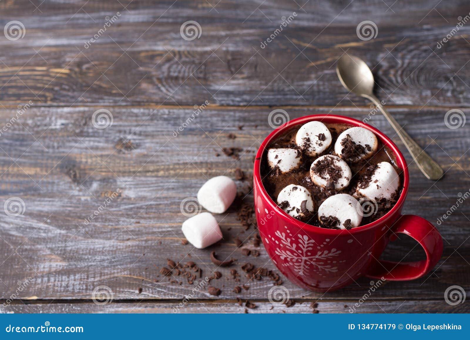 Chocolate quente com marshmallows e chocolate raspado em uma caneca vermelha em uma tabela de madeira