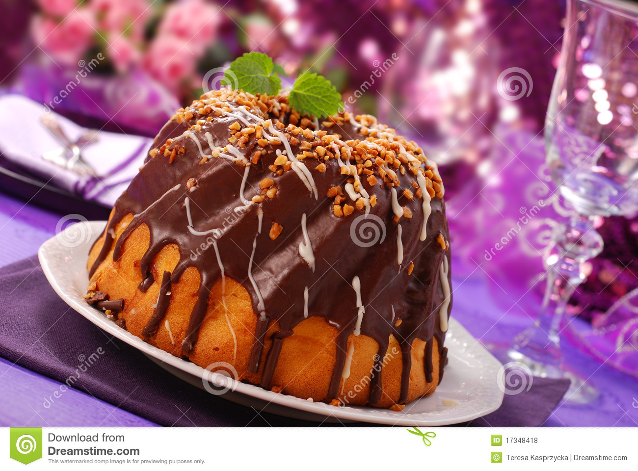 Chocolate ring cake with nuts topping for party on purple shining ...