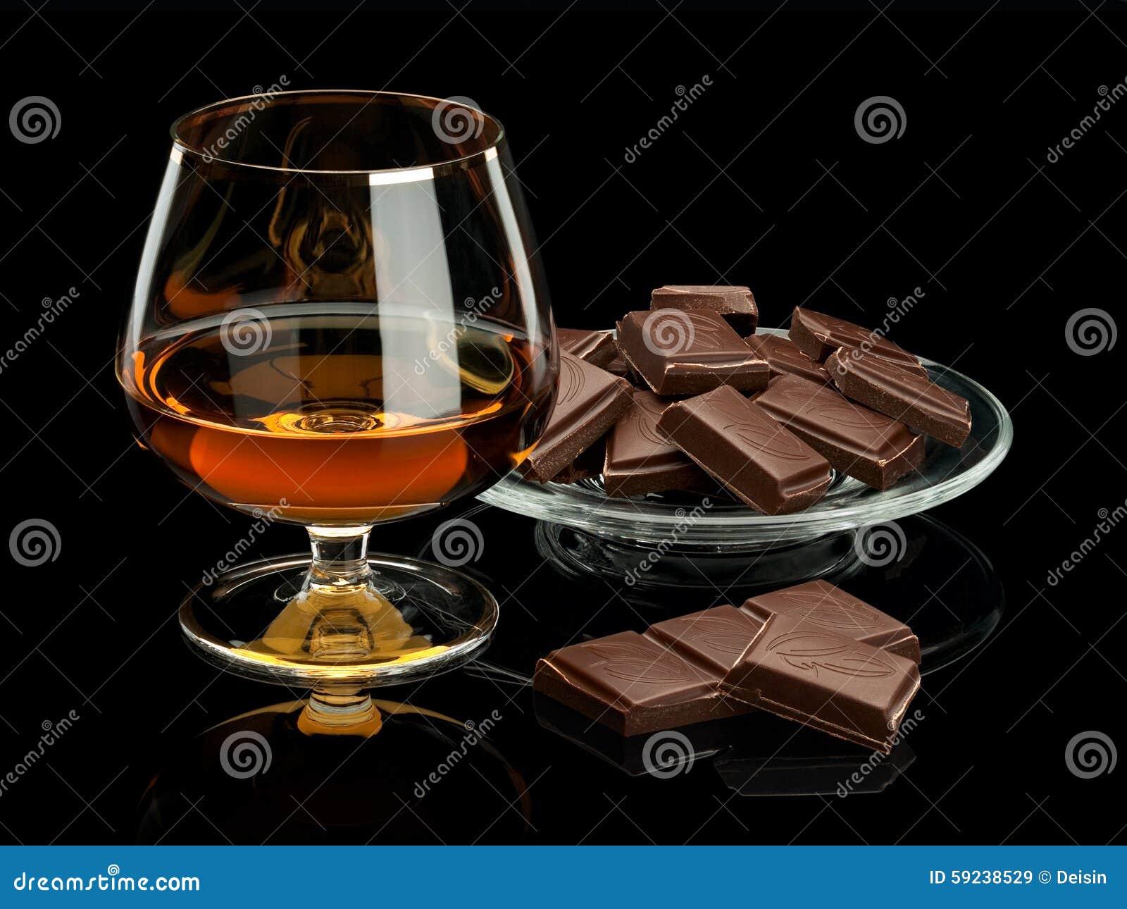Chocolate y coñac en cristalería se aísla en negro