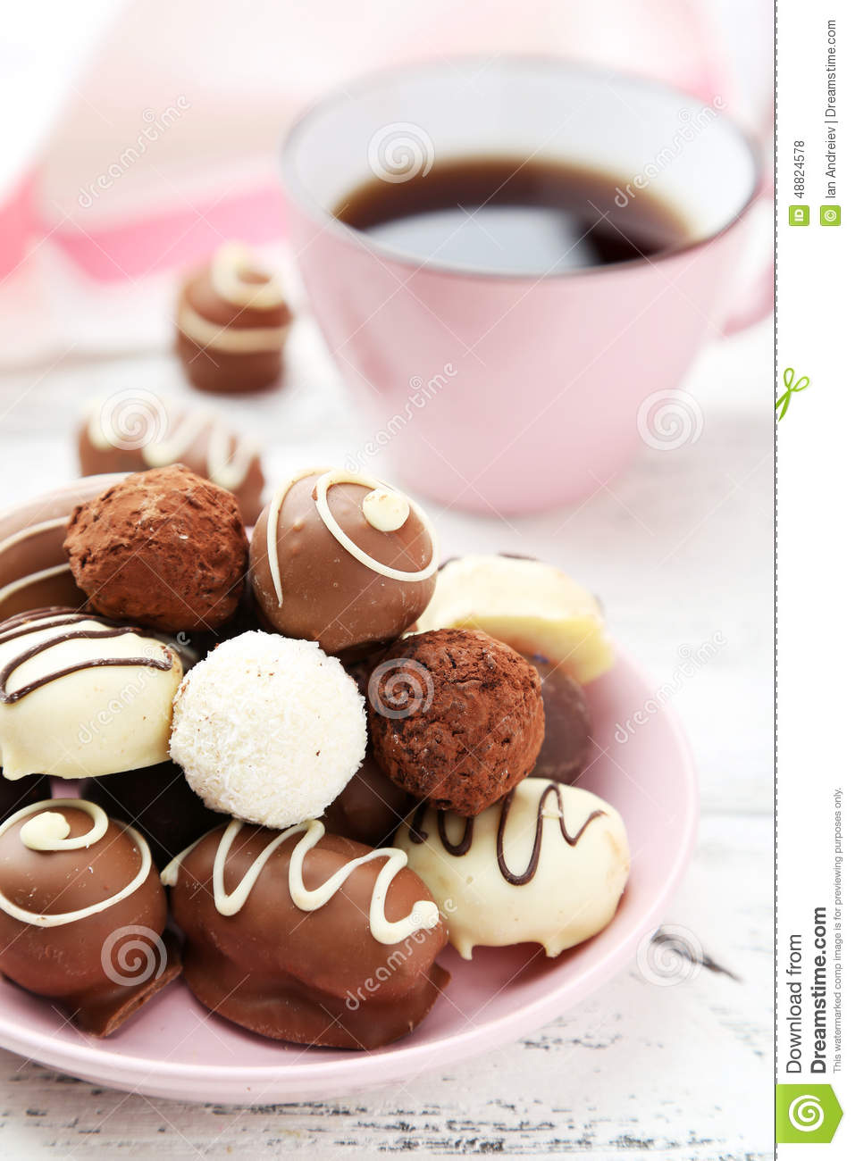 Chocolates in bowl on the white wooden background