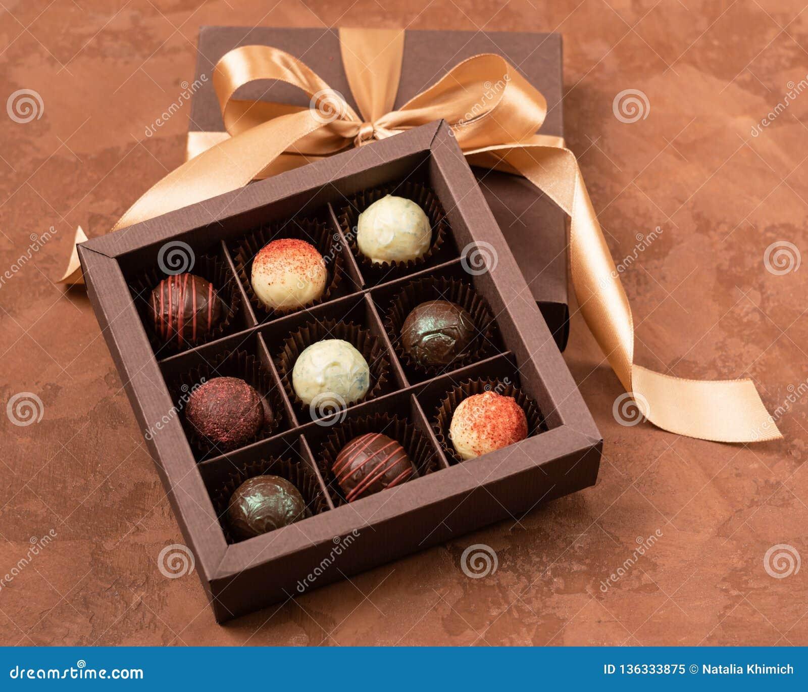 Chocolates finos na caixa do ofício com fita do cetim em um fundo escuro Disposição lisa Conceito festivo Copie o espaço