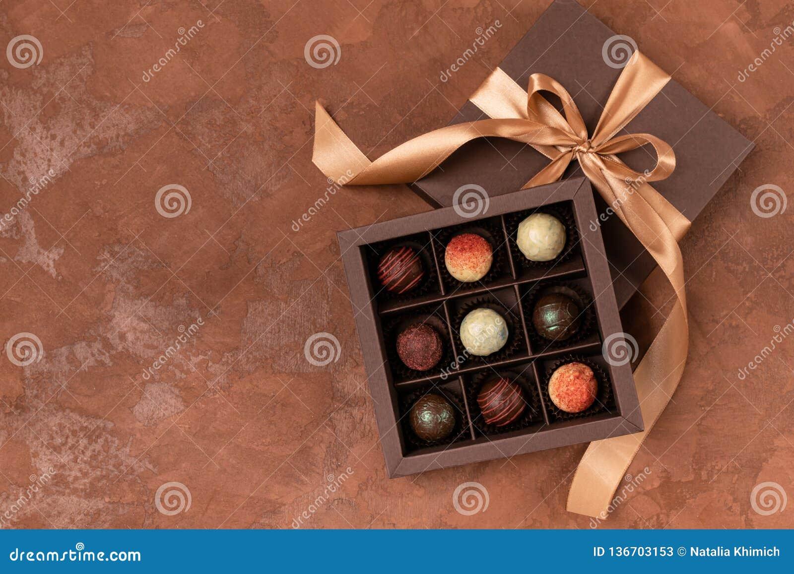 Chocolates finos na caixa do ofício com fita do cetim em um fundo escuro Lugar para o projeto Disposição lisa Conceito festivo