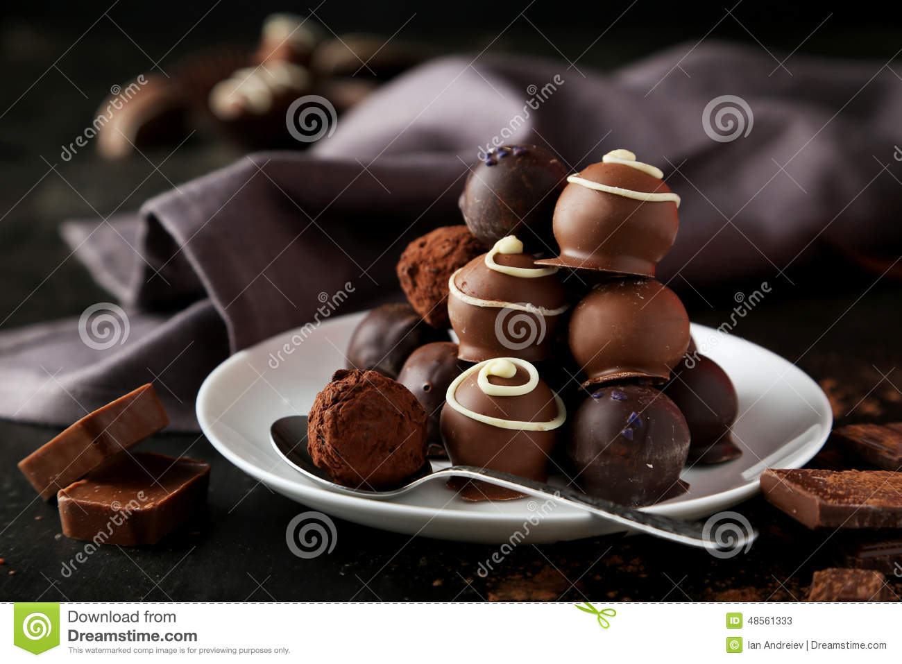 Chocolates on plate on the black background
